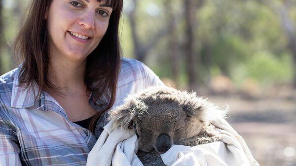 Валентина Мелла держит в руках коалу, пострадавшую от обезвоживания