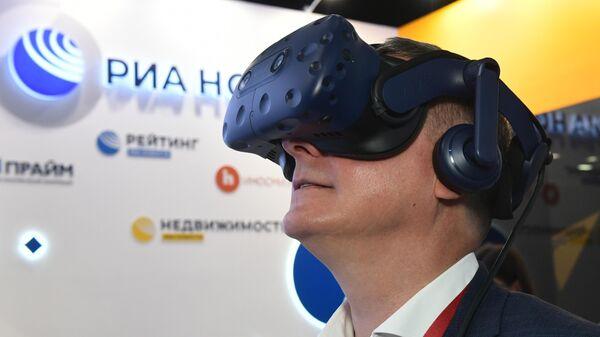 Руководитель Федерального агентства связи Олег Духовницкий VR очках виртуальной реальности на стенде МИА Россия сегодня во второй день ПМЭФ