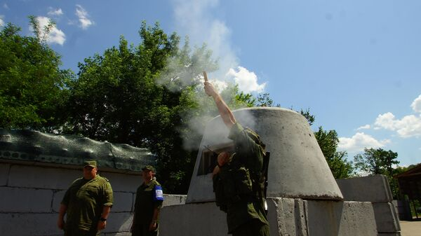 Военнослужащий ЛНР запускает сигнальную ракету белого цвета, означающую готовность ополченцев приступить к разведению сил и средств, на контрольно-пропускном пункте в районе Станицы Луганской