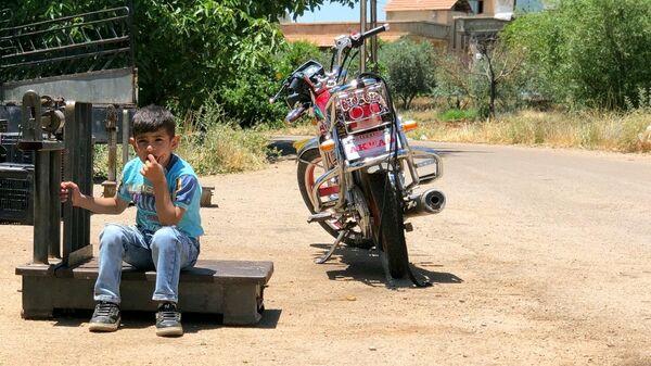 Мальчик сидит возле мотоцикла в поселении Бейт-Джинн
