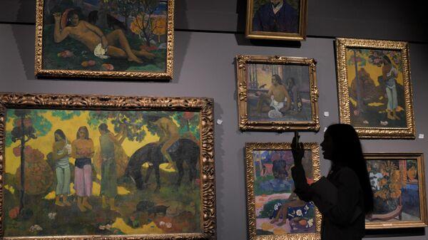 Посетительница фотографирует картину Поля Гогена Сбор плодов (слева) на пресс-показе выставки Щукин. Биография коллекции в ГМИИ