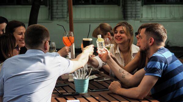 Посетители на летней веранде кафе в саду Эрмитаж в Москве