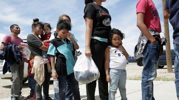 Мигранты стоят в очереди перед входом во временный лагерь после пересечения границы между Мексикой и США