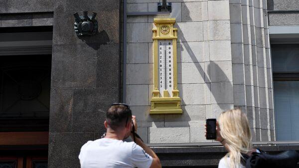 Молодые люди фотографируют термометр на здании Государственной Думы РФ в Москве