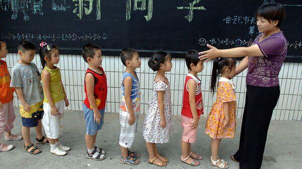 Учитель китайского языка с группой первоклассников в начальной школе в провинции Аньхой, Китай