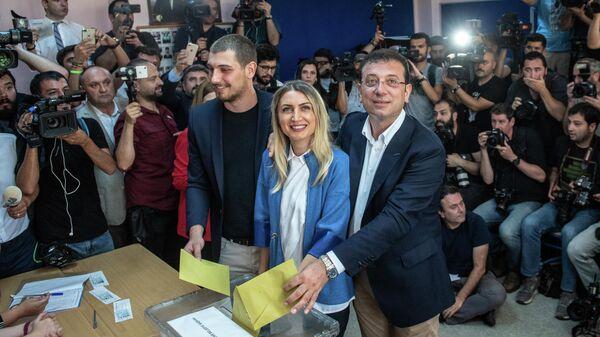 Кандидат в мэры Стамбула от главной оппозиционной Народно-республиканской партии  Экрем Имамоглу голосует вместе со своей женой и их сыном. 23 июня 2019