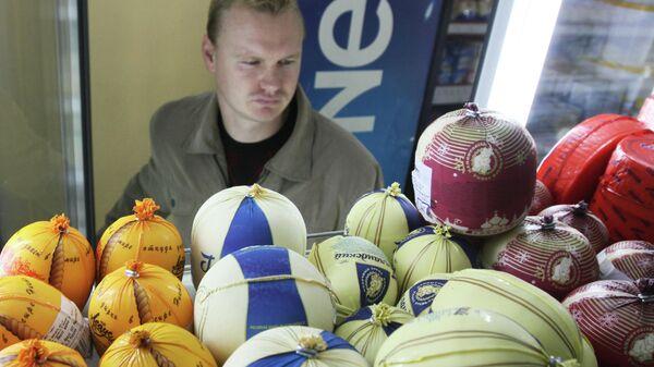 Мужчина у прилавка с сыром в супермаркете