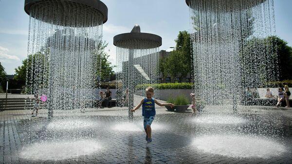 Ребенок играет в фонтане в Вильнюсе, Литва