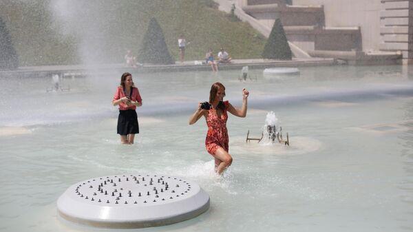 Женщины купаются в фонтане Трокадеро в Париже