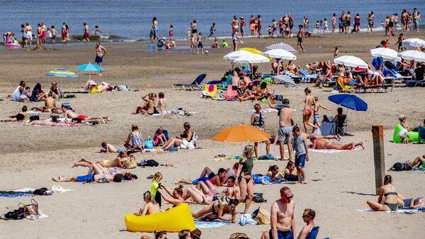Люди, загорающие на пляже в Нордвейке, Нидерланды