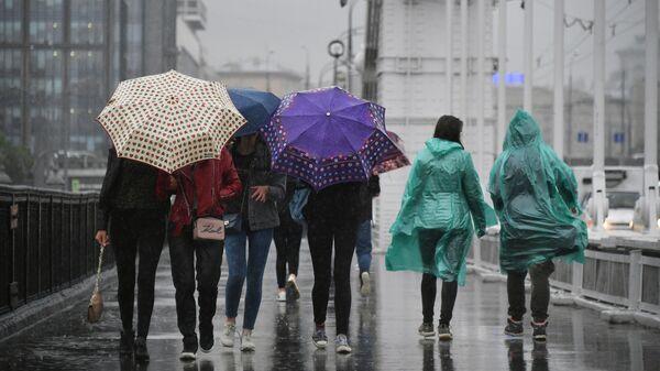 Пешеходы идут по Крымскому мосту во время дождя в Москве