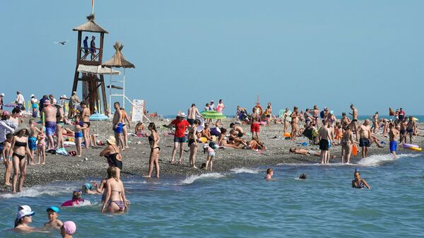 Отдыхающие на пляже в районе Адлер города Сочи