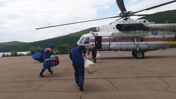 Сотрудники МЧС направляются к вертолету для облета подтопленных территорий в Иркутской области