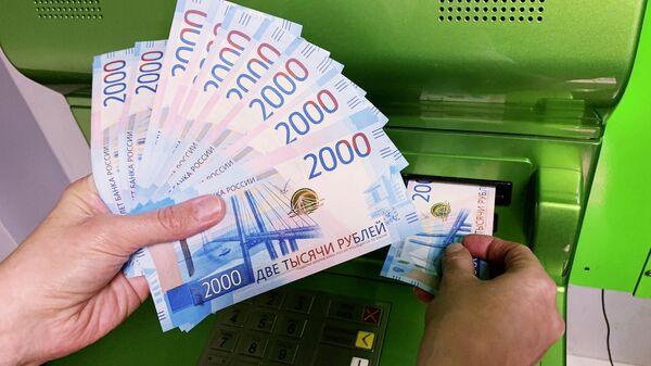 Клиент Сбербанка вносит наличные деньги в банкомат. Архивное фото