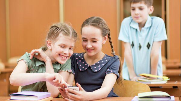 Школьники с мобильным телефоном в классе