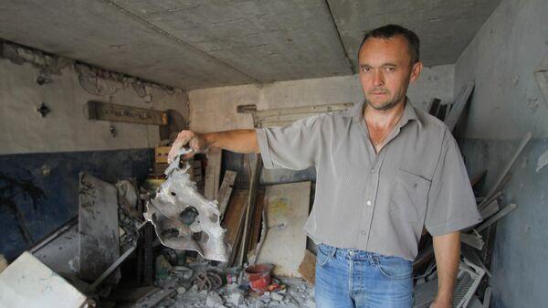 Владелец гаража в Горловке, разрушенного вследствие обстрела, демонстрирует фрагмент двери с отверстиями от снарядов. 8 июля 2019
