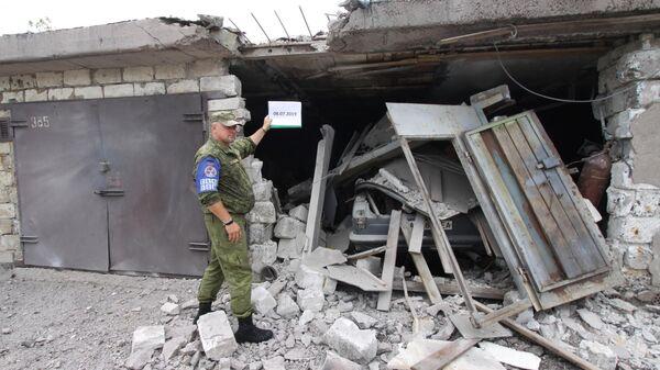 Офицер Совместного центра контроля и координации фиксирует повреждения гаражей в результате артобстрела Горловки. 8 июля 2019