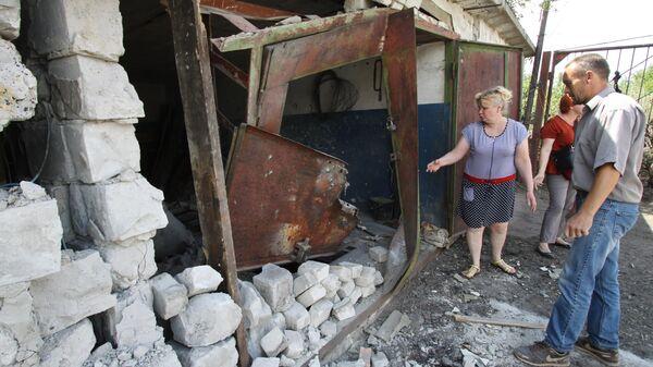 Жители Горловки у гаража, разрушенного вследствие обстрела. 8 июля 2019