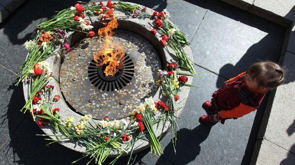 Ребенок у Вечного огня во время праздничных мероприятий, посвященных годовщине Победы в Великой Отечественной войне в Великом Новгороде