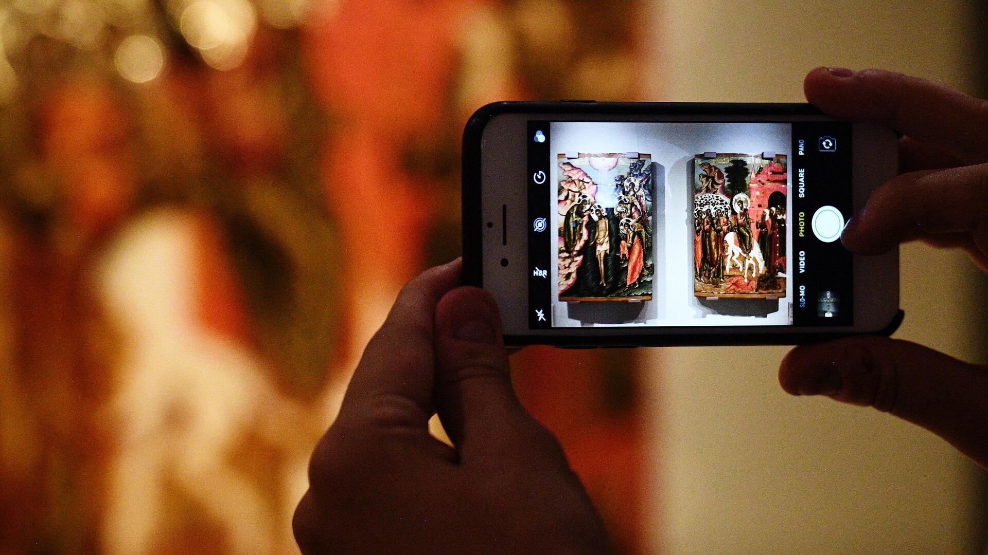 Посетитель выставки Хранители времени. Реставрация в Музеях Московского Кремля фотографирует икону Богоявление (слева) и икону Вход в Иерусалим - РИА Новости, 1920, 14.04.2020