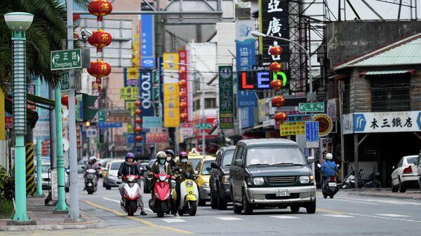 Мотоциклисты и автомобили у пешеходного перехода на одной из улиц города Цзилун