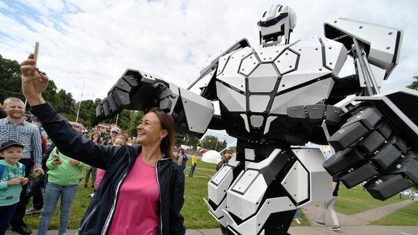 Женщина фотографируется с трансформером автоботом на фестивале науки и технологий Geek Picnic 2019 Жить вечно/Immortality