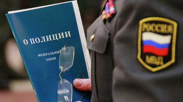 Брошюра с законом О полиции в руках сотрудника МВД
