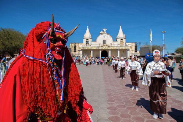 Танцоры в традиционных костюмах во время карнавала на улицах Ла Тираны, Чили