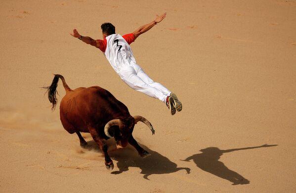 Рекортадор прыгает через быка на фестивале Сан-Фермин в Памплоне, Испания