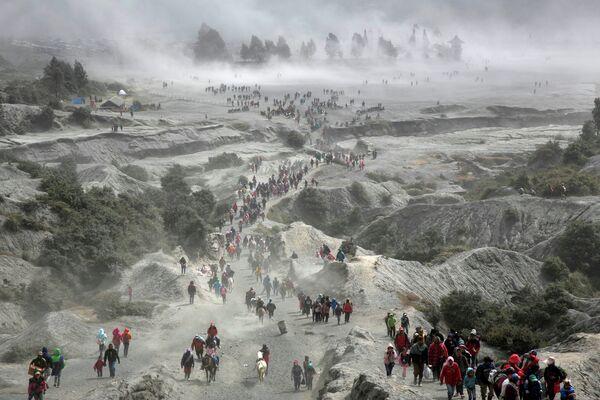 Тенгеры и туристы у вулкана Бромо во время фестиваля Yadnya Kasada в Индонезии