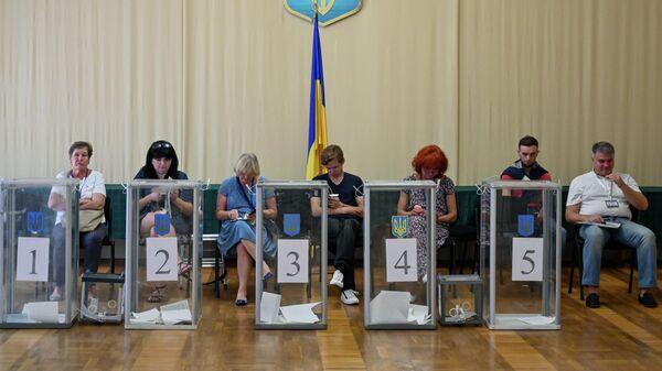 Наблюдатели на избирательном участке в Киеве во время голосования на досрочных выборах в Верховную раду Украины. 21 июля 2019