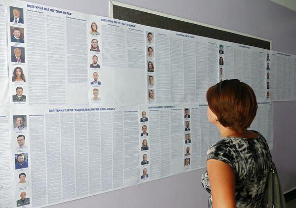 Женщина изучает списки кандидатов на пост депутата в Верховную раду Украины на участке в Черкассах