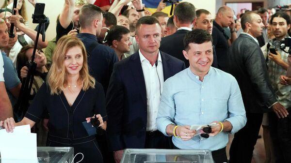 Президент Украины Владимир Зеленский с супругой во время голосования на внеочередных выборах в Верховную раду