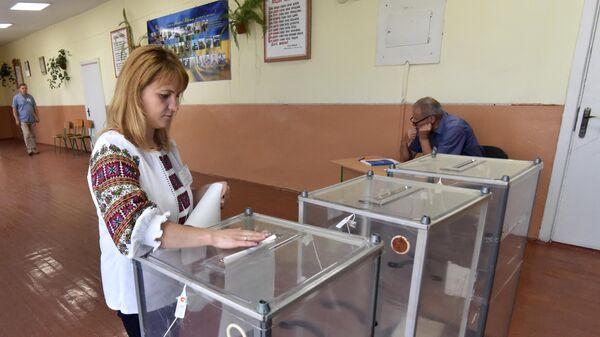 Девушка голосует на досрочных выборах в Верховную раду Украины на избирательном участке в селе Крехов Львовской области