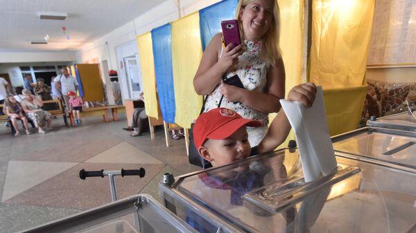 Мальчик опускает бюллетень в урну на избирательном участке во Львове в день досрочных выборов в Верховную раду Украины