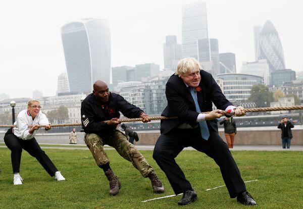Мэр Лондона Борис Джонсон принимает участие в перетягивании каната вместе с военнослужащими. 27 октября 2015 года
