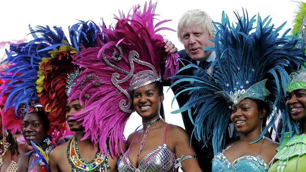 Мэр Лондона Борис Джонсон позирует с танцорам во время карнавала в Ноттинг Хилле. 24 августа 2011 года