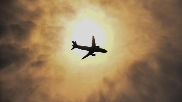 Самолет в небе над Новосибирском. Смог вызван действующими лесными пожарами на территории Красноярского края.