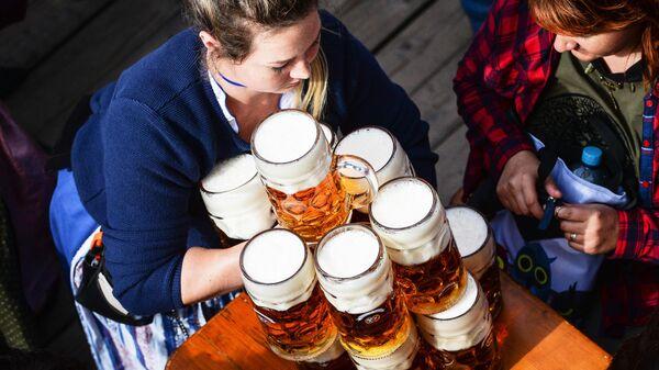 Официантка разносит бокалы с пивом