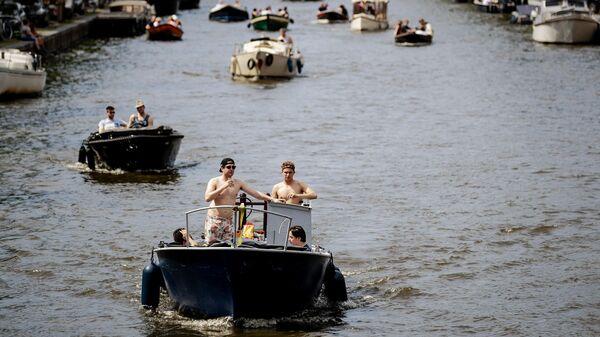 Лодки плывут по каналу в центре Амстердама