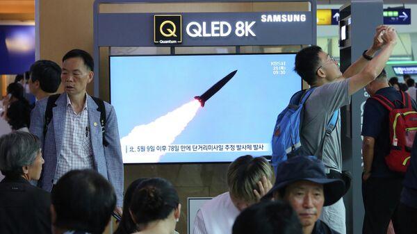 Жители Сеула смотрят по телевизору выпуск новостей о запуске ракет с территории КНДР