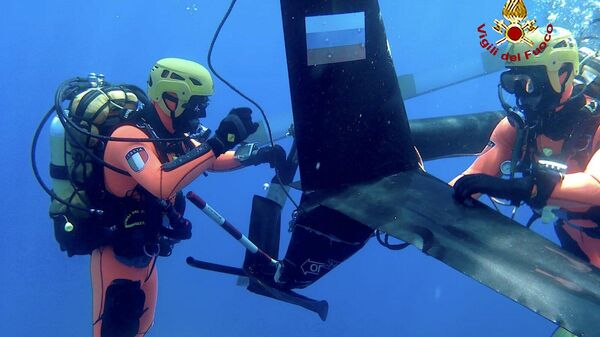 Спасатели на месте крушения вертолета у Robinson R66 у побережья Тосканы, Италия