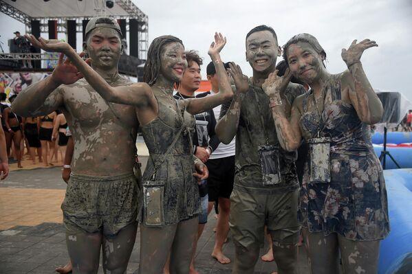 Туристы возле бассейна с грязью на пляже Тэчхон во время фестиваля вблизи города Порен