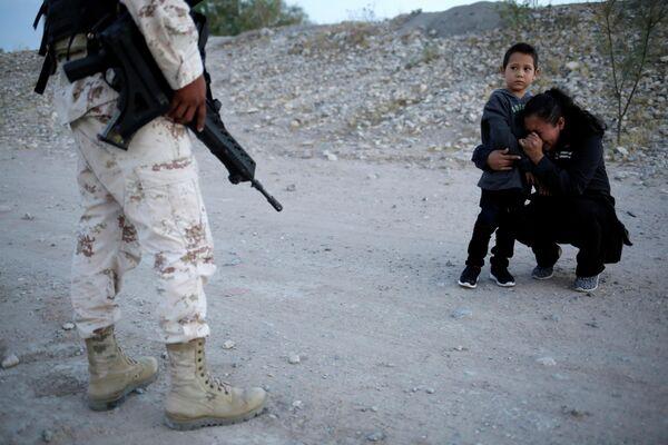 Женщина с ребенком стоят перед сотрудником национальной гвардии Мексики возле границы с США