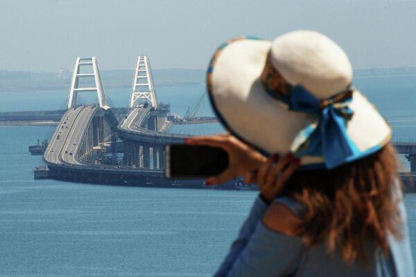 Девушка фотографирует Крымский мост через Керченский пролив