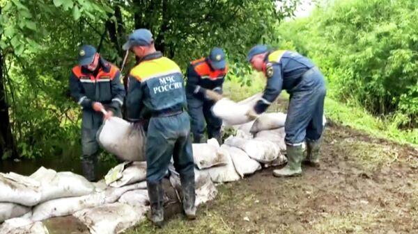Сотрудники МЧС РФ укладывают мешки с песком в подтопленном районе Амурской области.