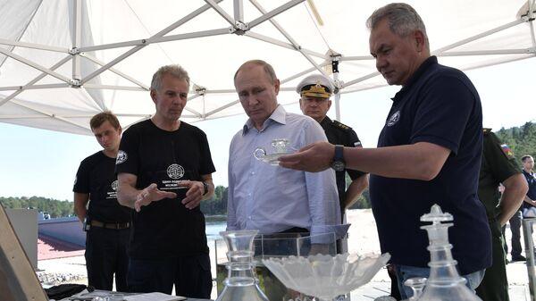 Президент РФ Владимир Путин и министр обороны РФ Сергей Шойгу во время осмотра коллекции посуды с борта судна, которое затонуло в XIX веке у побережья острова Гогланд в Финском заливе