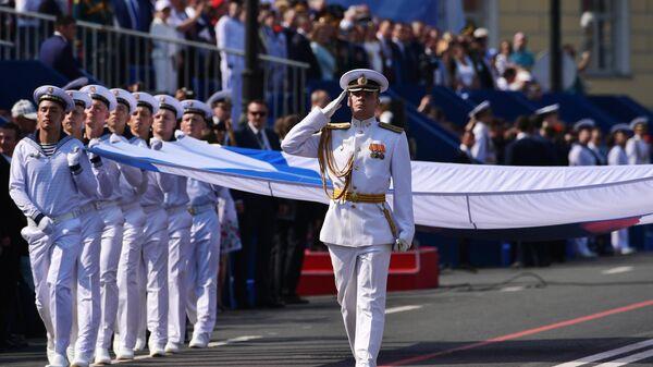 Военнослужащие маршируют с Андреевским флагом на главном военно-морском параде, посвященном Дню ВМФ в Санкт-Петербурге.