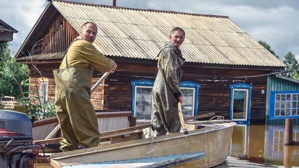 Местные жители плывут на лодке по  затопленной улице в селе Норск в Селемджинском районе Амурской области