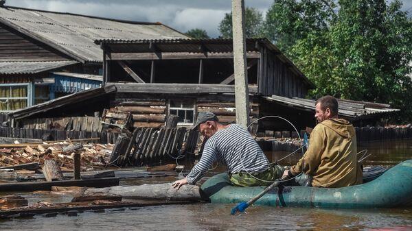 Местные жители плывут на лодке по  затопленной улице в Амурской области